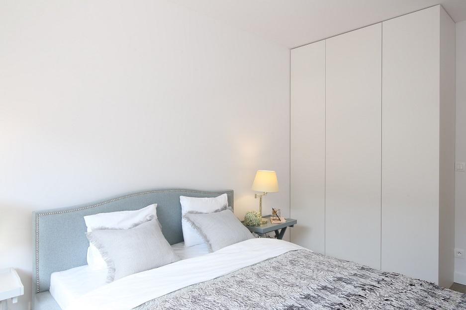 biała sypialnia z dużą szafą
