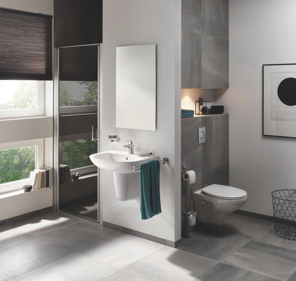 Łazienka w odcieniach szarości z toaletą, umywalką i kabiną prysznicową