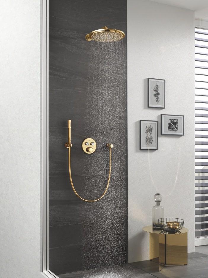 Złota deszczownica na tle czarnych płytek - obok prysznica na jasnej ścianie wiszą obrazki