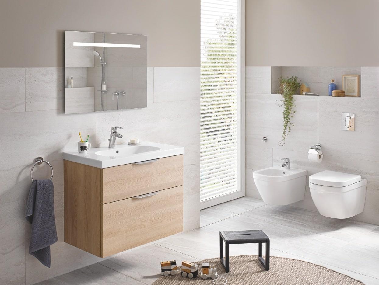 Jasna łazienka z umywalką, okrągłym lustrem, prysznicem i toaletą z przyciskiem spłukującym