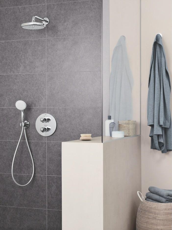 Prysznic z deszczownicą w łazience z ciemnymi kafelkami; obok półka z przyborami i zawieszony na jasnej ścianie ręcznik.