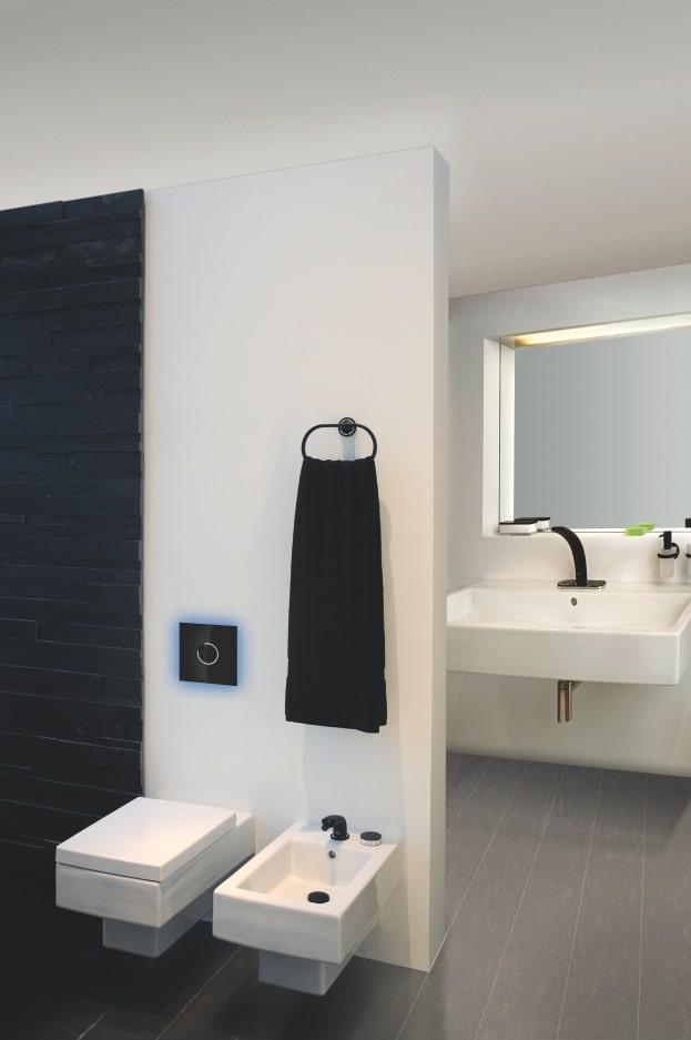 Jasna łazienka z ciemnymi drzwiami i przyciskiem spłukującym nad białą toaletą - w tle umywalka i lustro