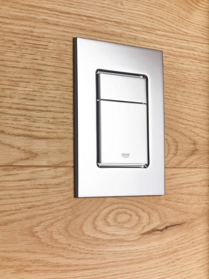 Kwadratowy przycisk spłukujący GROHE na tle drewnianych paneli