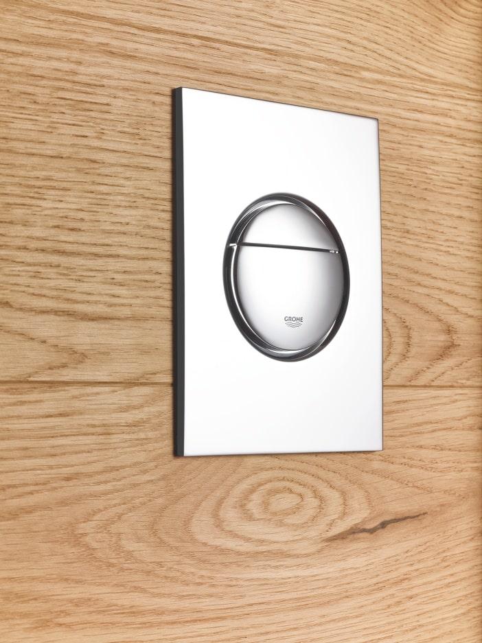 Okrągły przycisk spłukujący GROHE na drewnianych płytkach