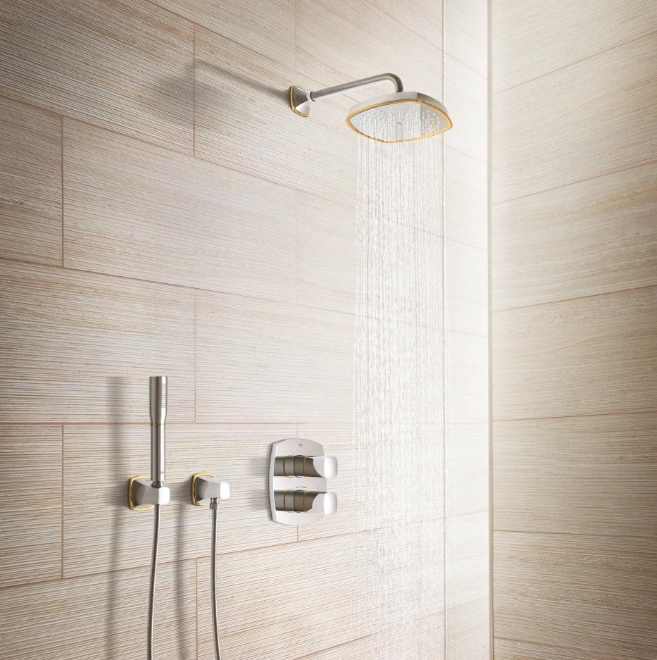 Prysznic z deszczownicą, z którego leje się woda - w tle jasne płytki.
