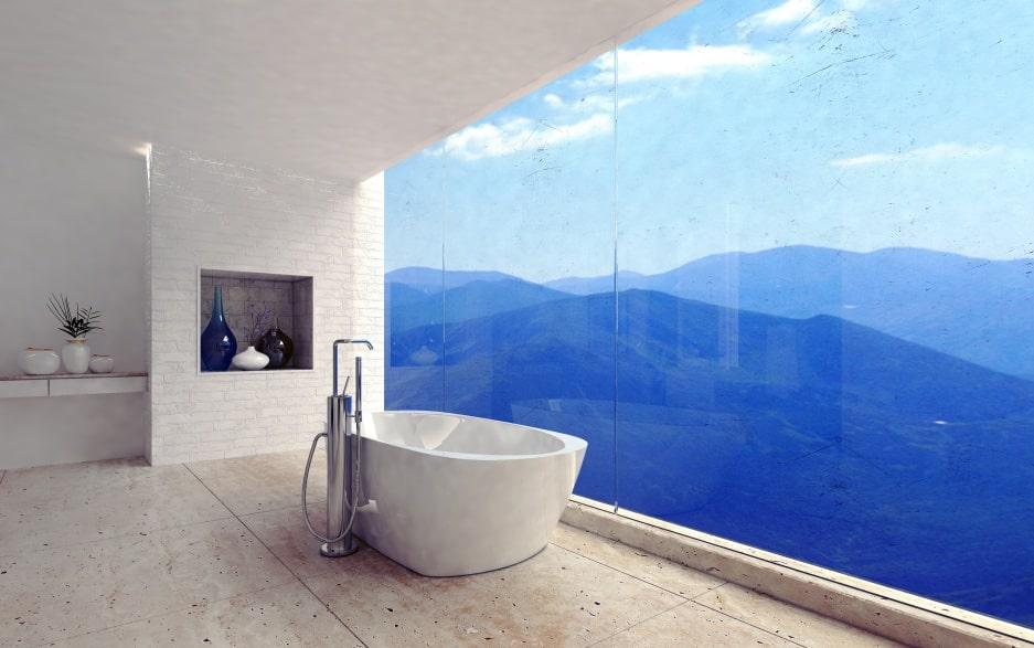 Z tyłu widać wnękę w łazience z wazonami, na pierwszym planie jest biała wanna i widok na góry